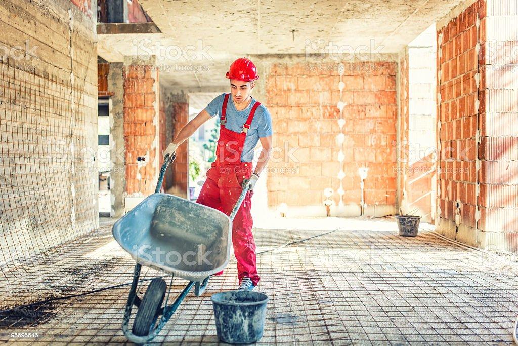 worker with empty wheelbarrow on construction site stock photo