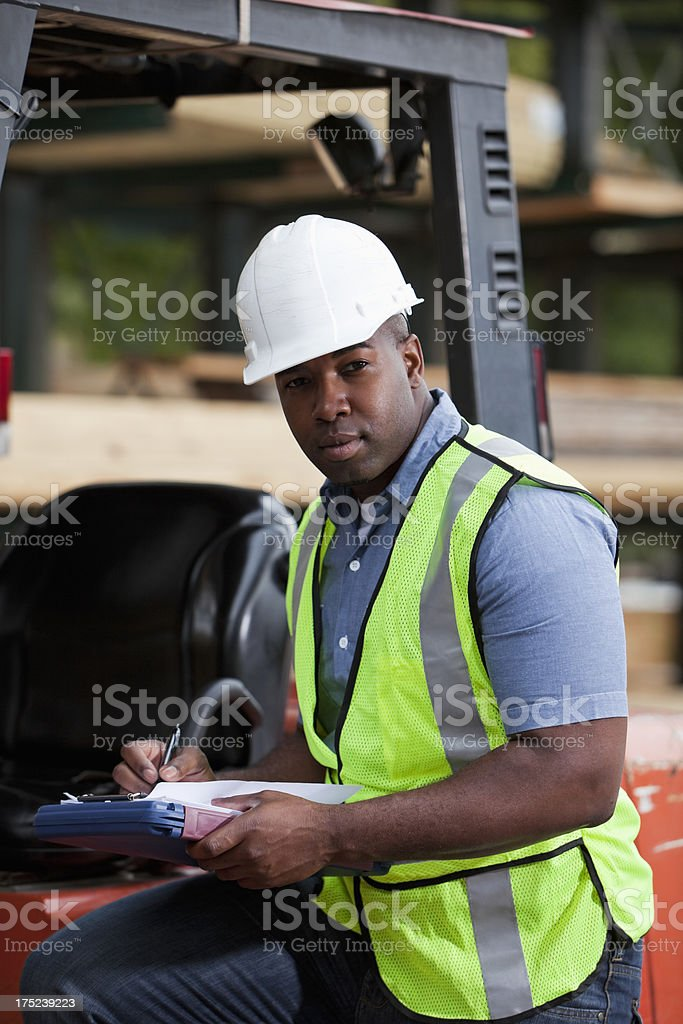 Worker with forklift holding clipboard stock photo