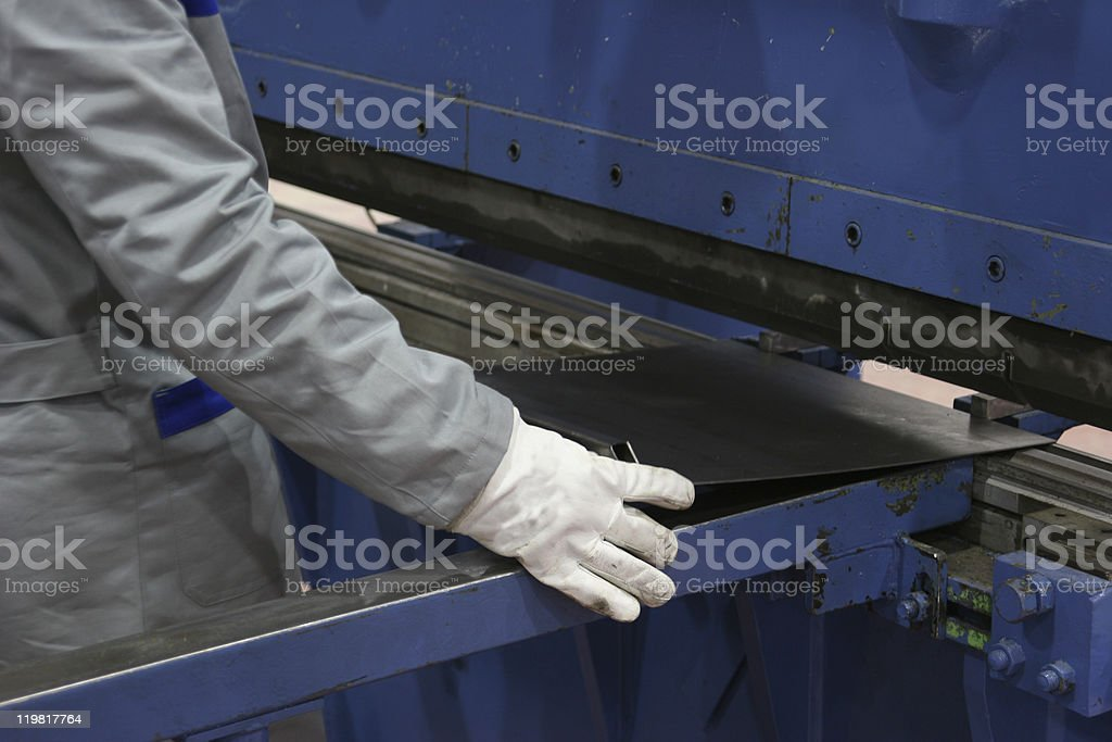 Worker with gloved hand using blue machinery stock photo