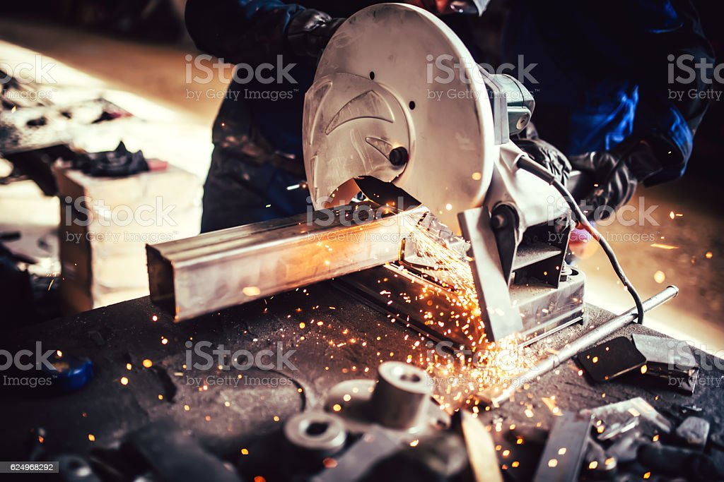 worker with grinding machine, power tool in factory stock photo