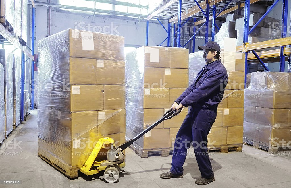 worker with hand pallet truck stacker at warehouse stock photo