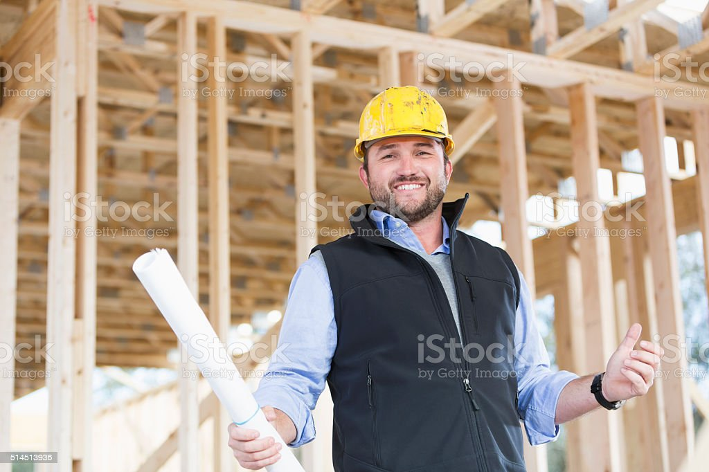 Worker with hardhat and plans at construction site stock photo