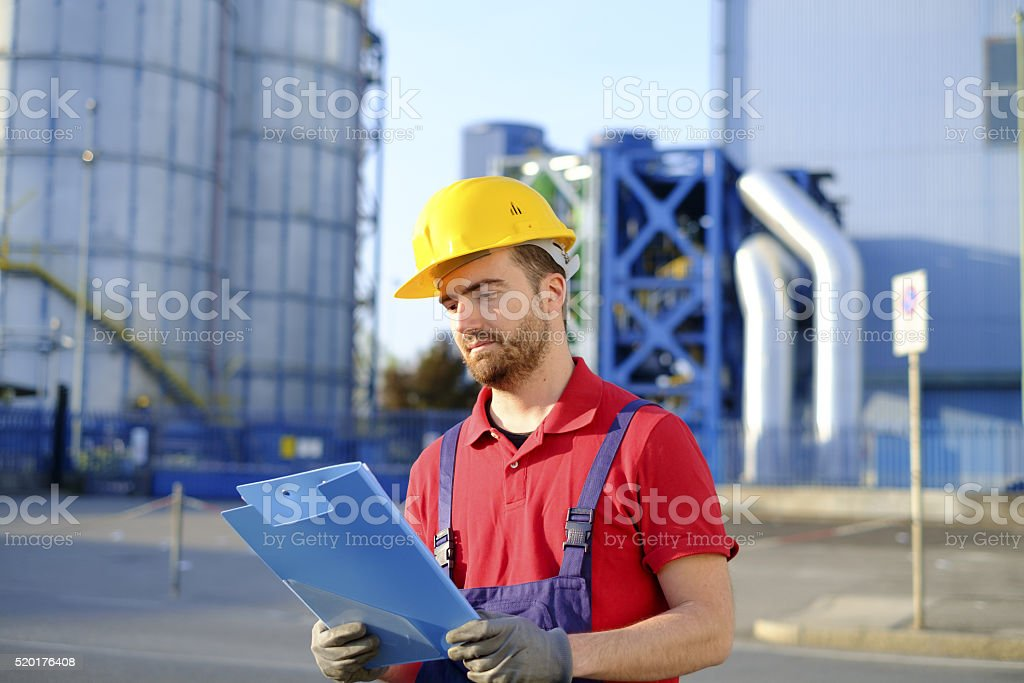 Worker with helmet working outside a modern factory stock photo