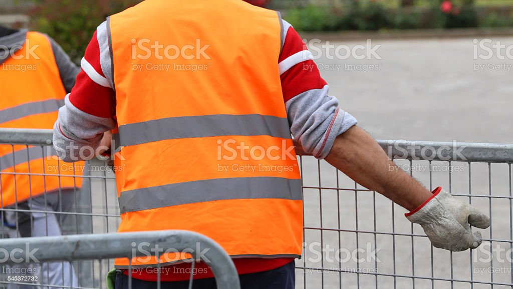 worker with high gloves moves hurdles before the concert event stock photo