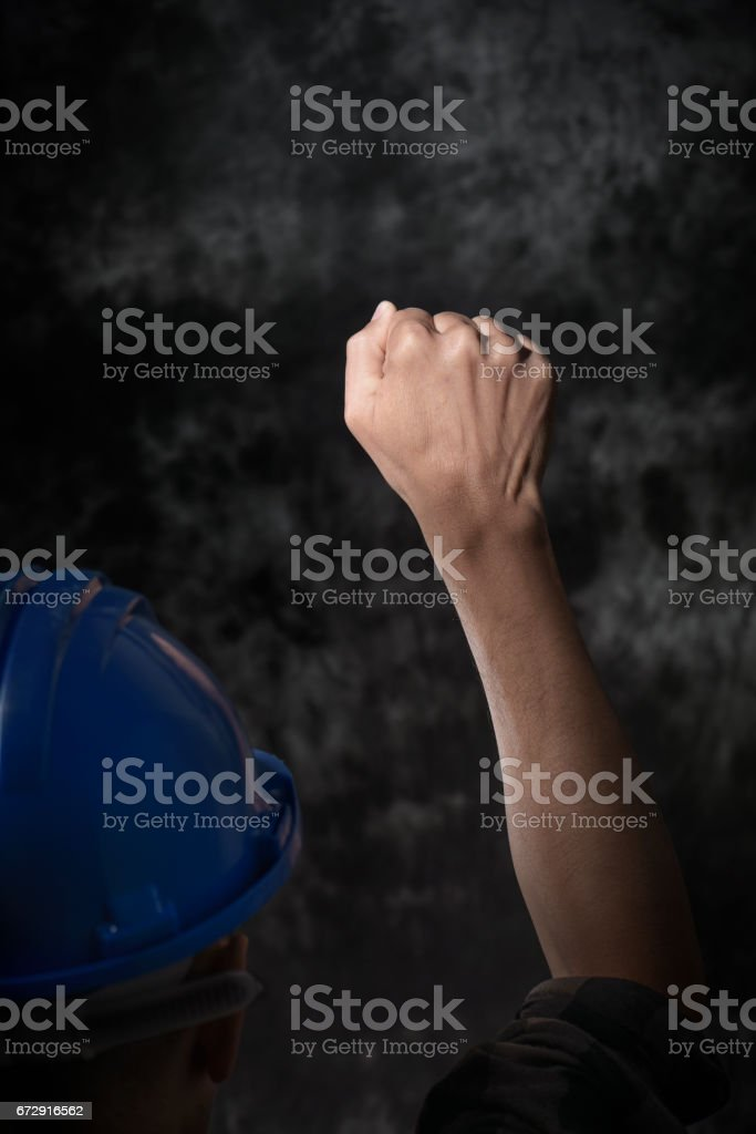worker with his fist raised to the air stock photo