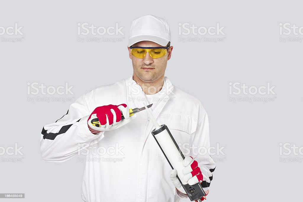 Worker with knife remove cut cap sealant silicon stock photo