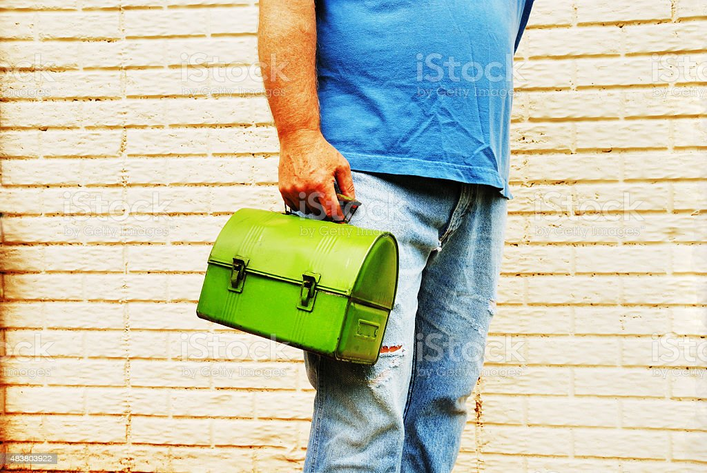 Worker with lunch box in torn jeans stock photo