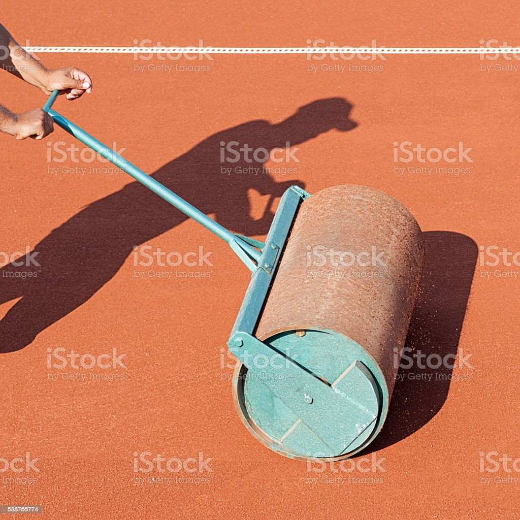 Worker with roller editing clay tennis court stock photo