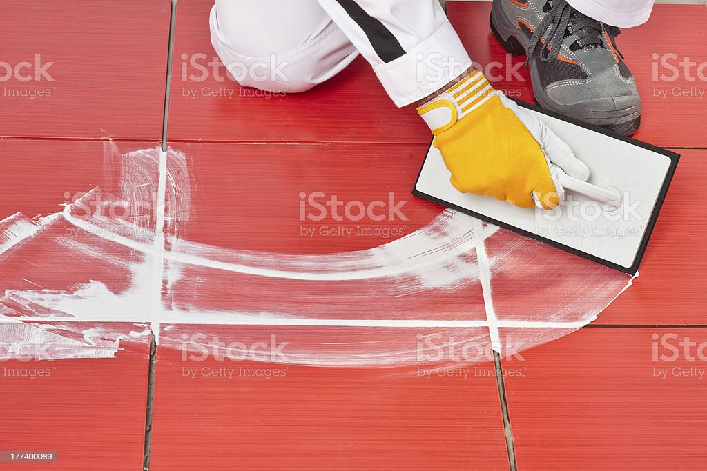 worker with rubber trowel applying grout tile stock photo