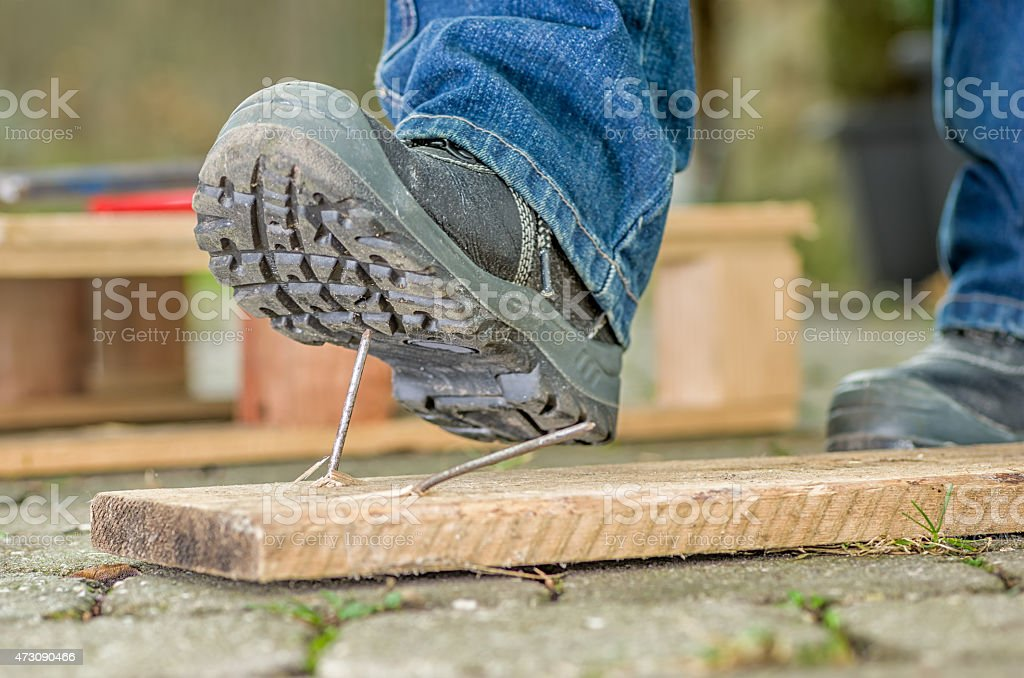 Worker with safety boots steps on a nail stock photo