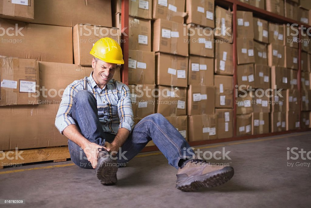Worker with sprained ankle on floor in warehouse stock photo
