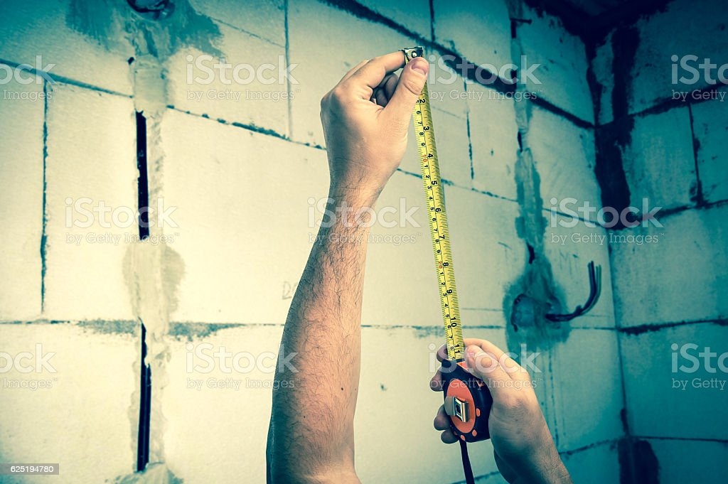 Worker with tape measure in centimeters and feets stock photo