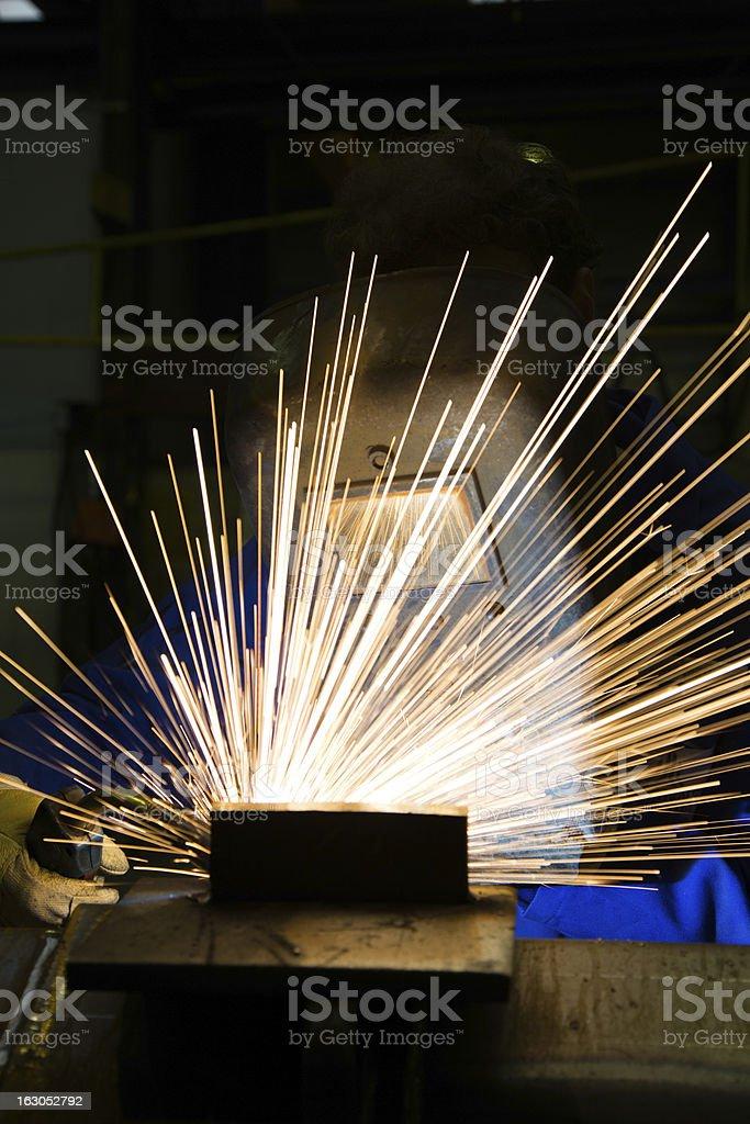 Worker with welding helmet welds steel royalty-free stock photo