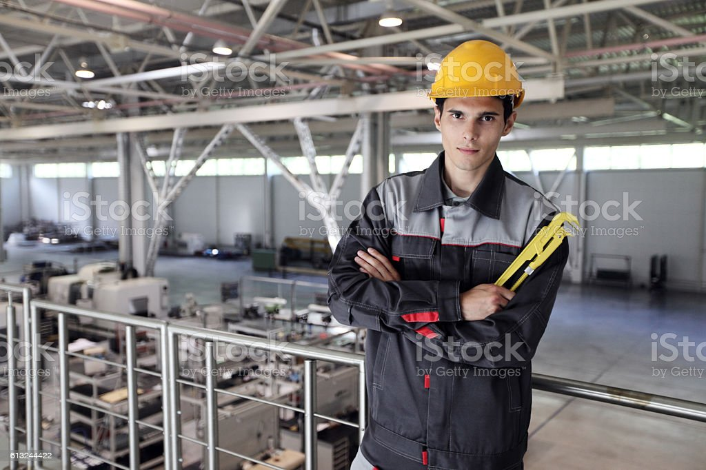 Worker with wrench at factory stock photo