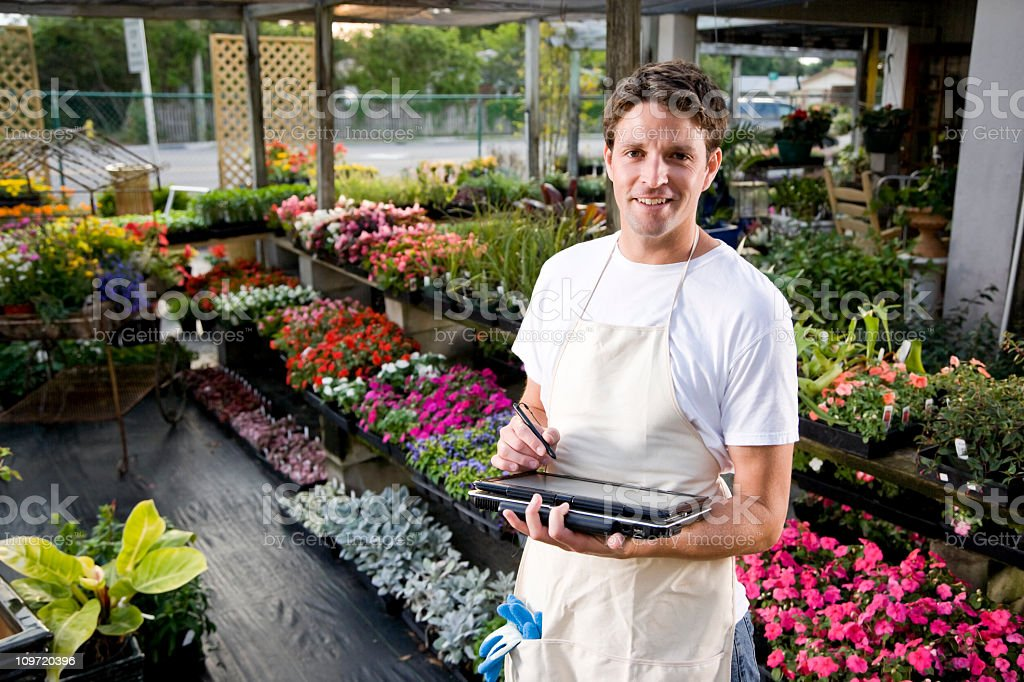 Worker working in plant nursery with laptop stock photo