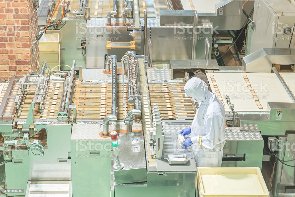 Worker working with machine in cookie factory stock photo