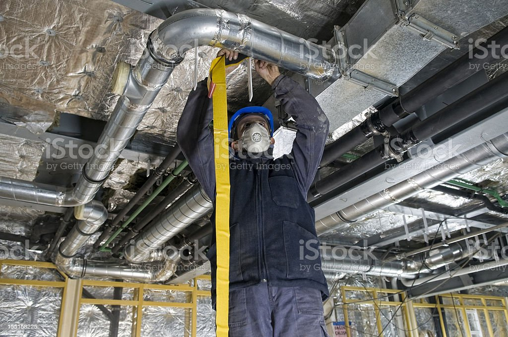 Worker wrapping an HVAC air duct with foil tape stock photo