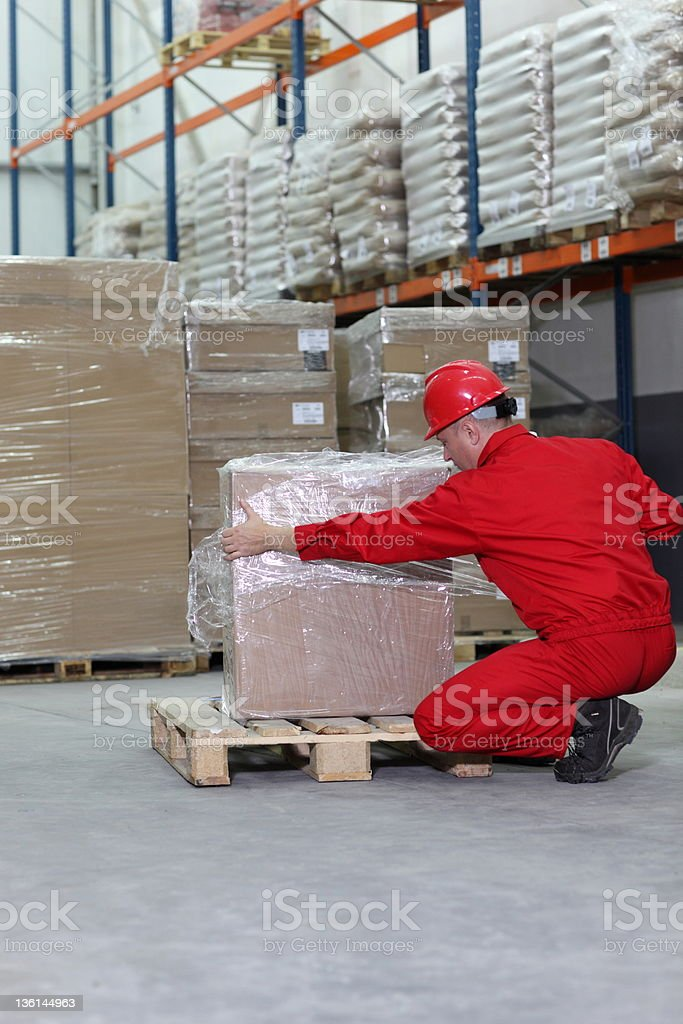 worker wrapping box on wooden pallet in warehouse royalty-free stock photo