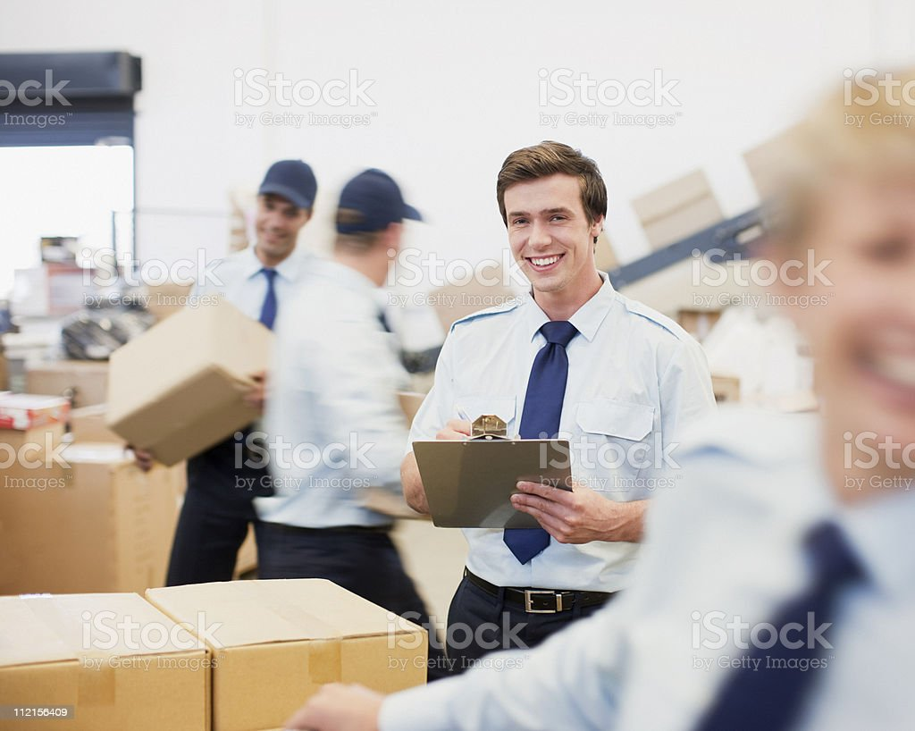 Worker writing on clipboard in shipping area stock photo