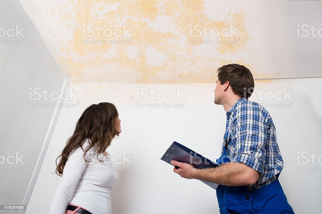 Worker Writing On Clipboard With Woman In House stock photo