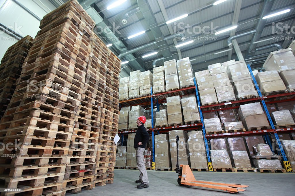 worker,hand pallet truck, stack of wooden pallets in storehouse stock photo