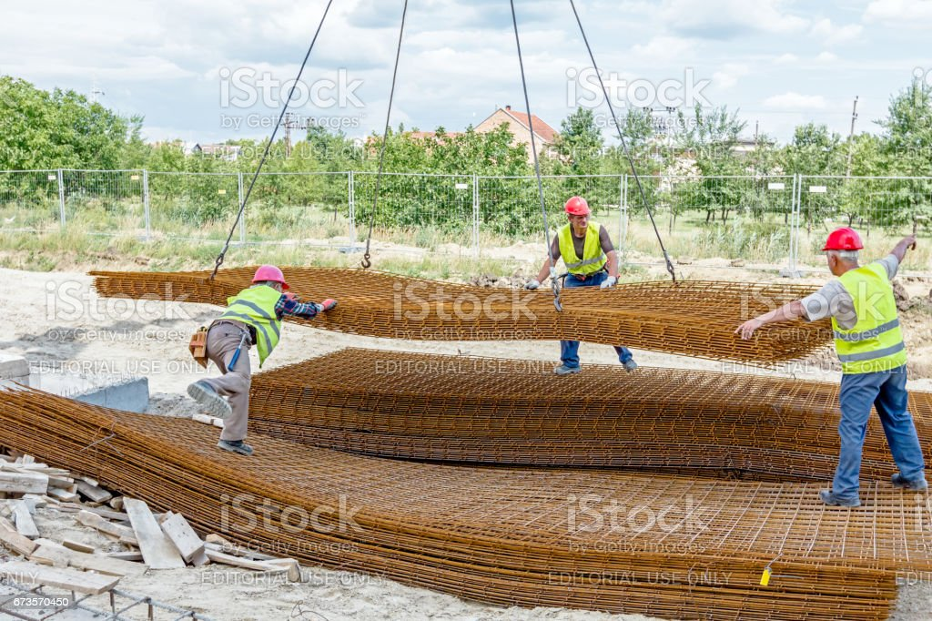 Workers are helping mobile crane to pile up of armature, rusty square reinforcement stock photo