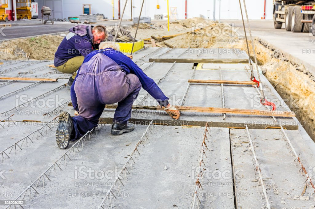 Workers are helping on ground, mobile crane is carry cement slab stock photo