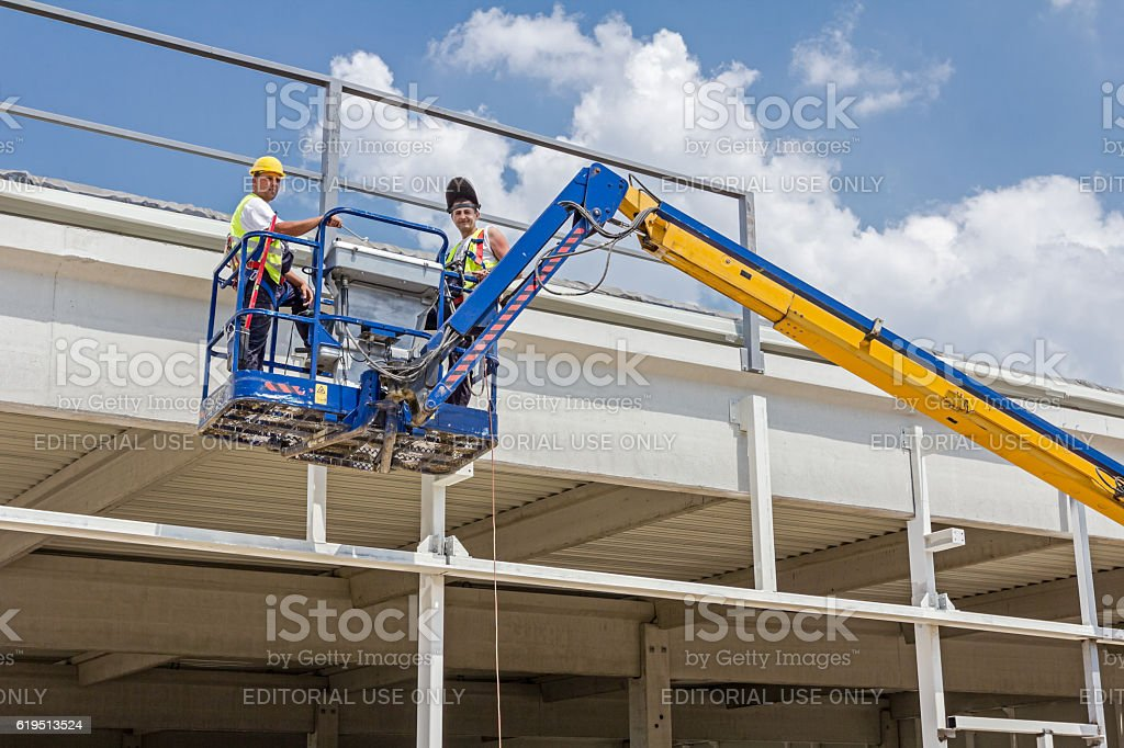 Workers are high up in cherry picker on building site. stock photo