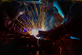 workers are welding auto part in factory
