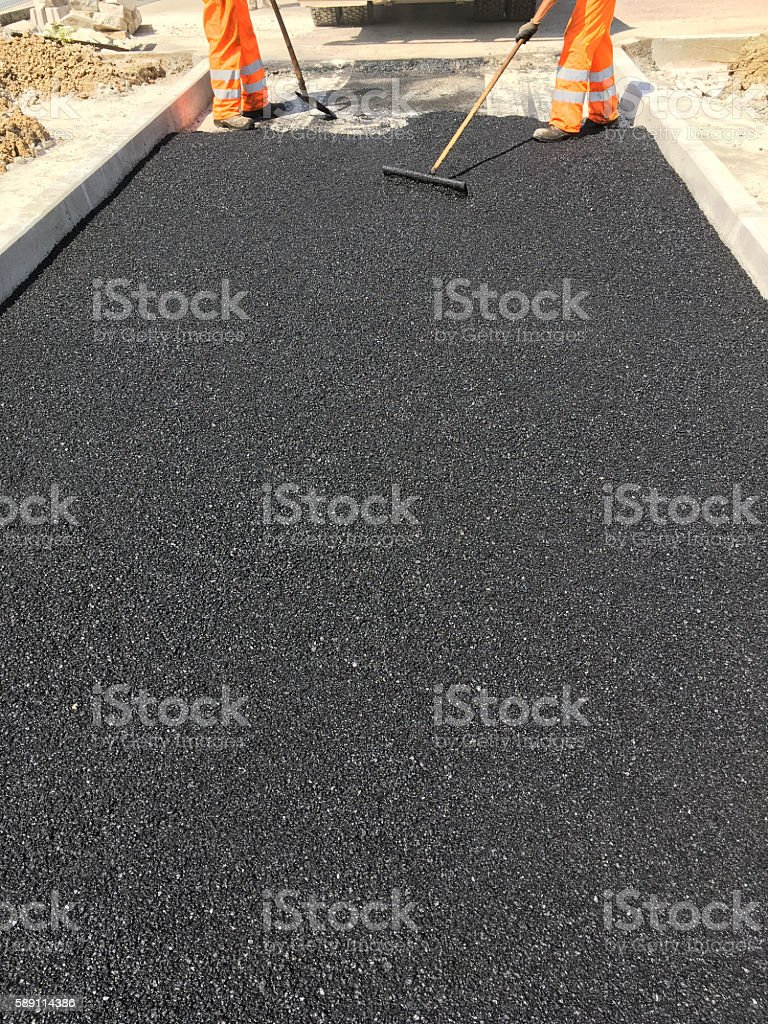 Workers asphalt a road in summer stock photo