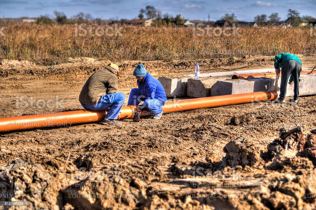 Workers Assembling a Drainage Pipe - HDR Image stock photo