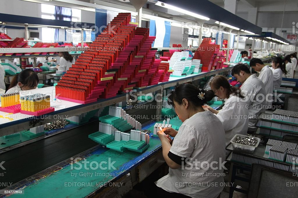 Workers assembling and testing lighters in factory. stock photo