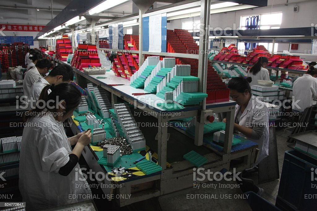 Workers assembling lighters in factory. stock photo