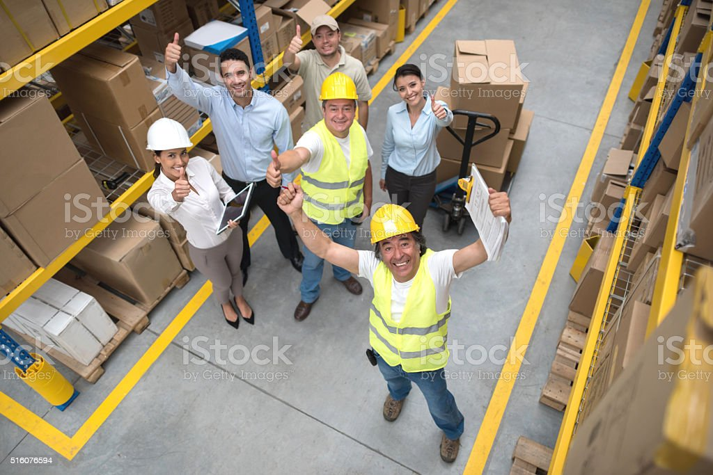 Workers at a warehouse with thumbs up stock photo