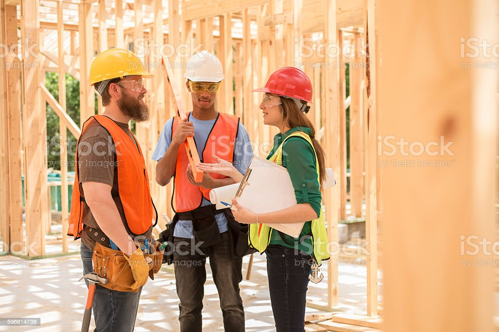 Workers at construction job site inside framed building. stock photo