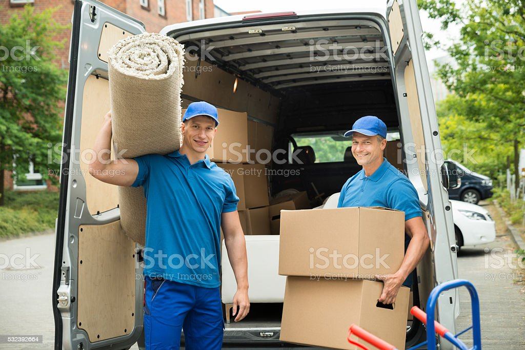 Workers Carrying Carpet And Cardboard Boxes stock photo