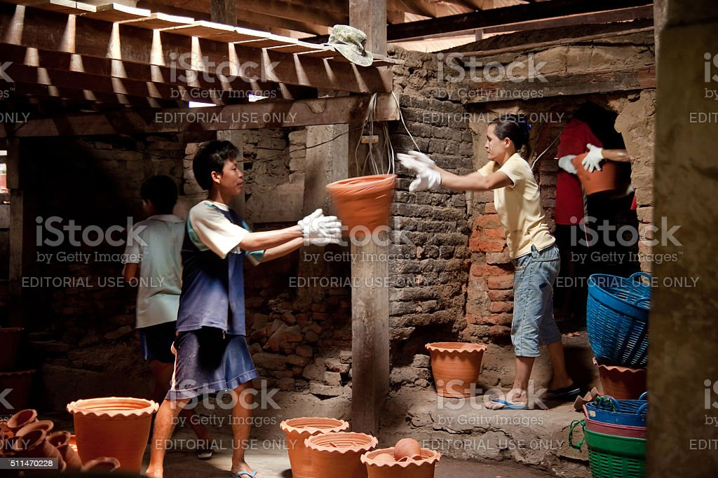 Workers carrying clay pots out of the kiln. stock photo