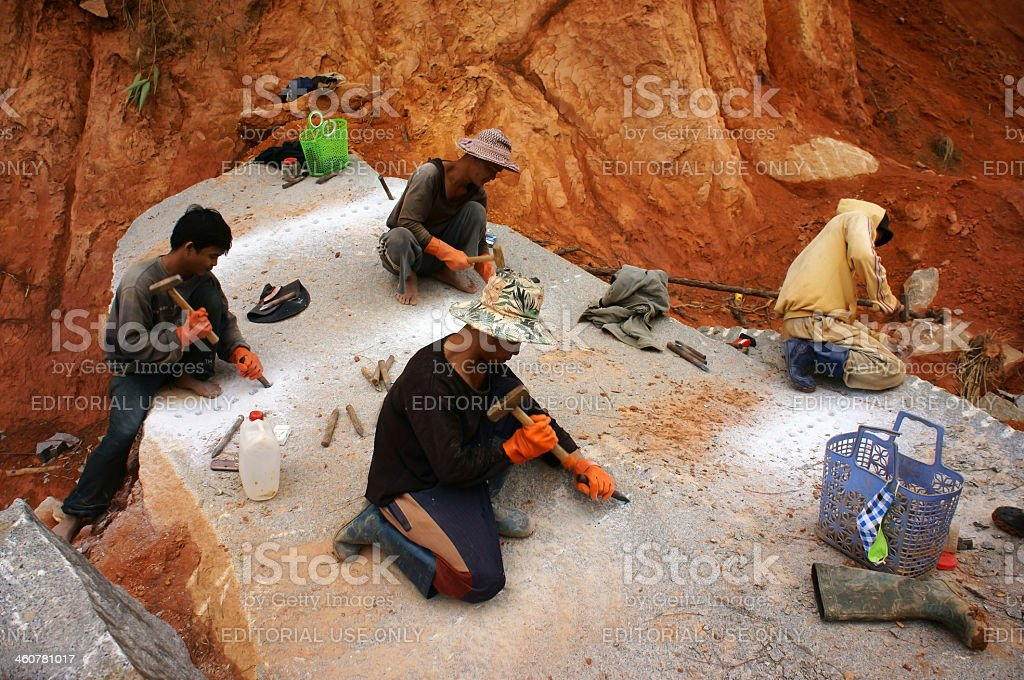 Workers carve out large rock  by hammer and splitter stock photo
