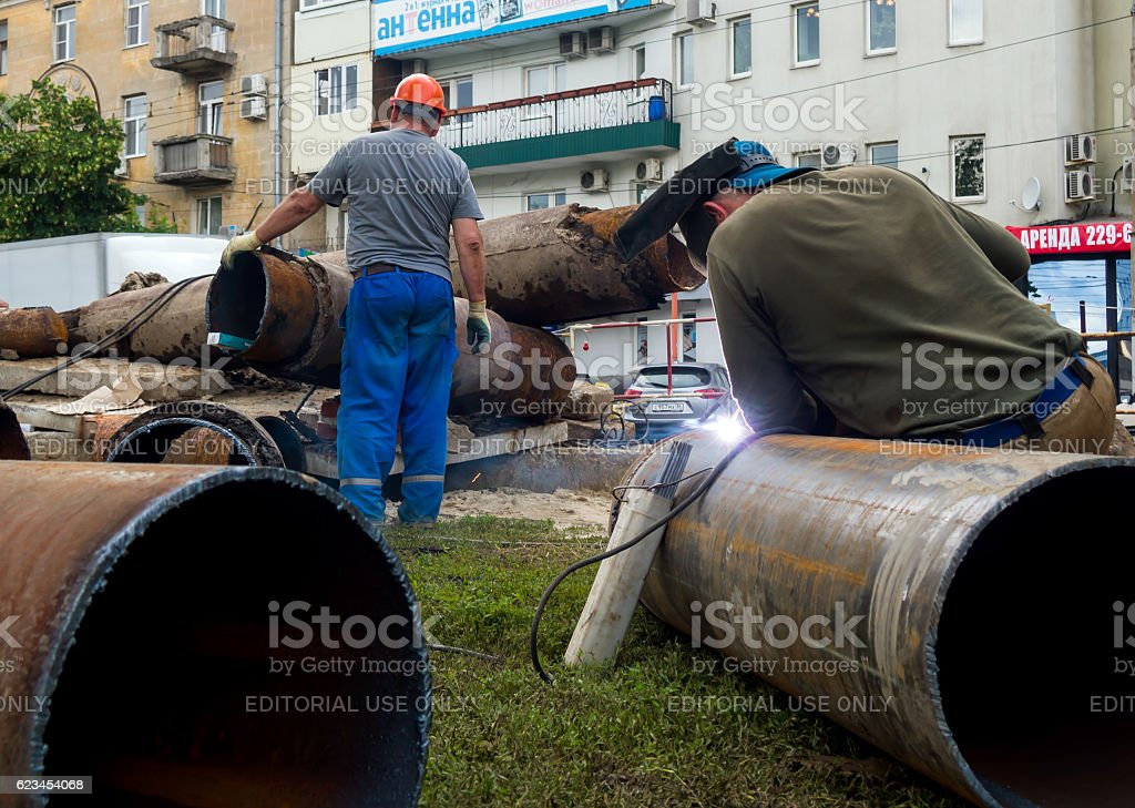 Workers changing mains pipe heat supply in the city stock photo