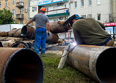Workers changing mains pipe heat supply in the city