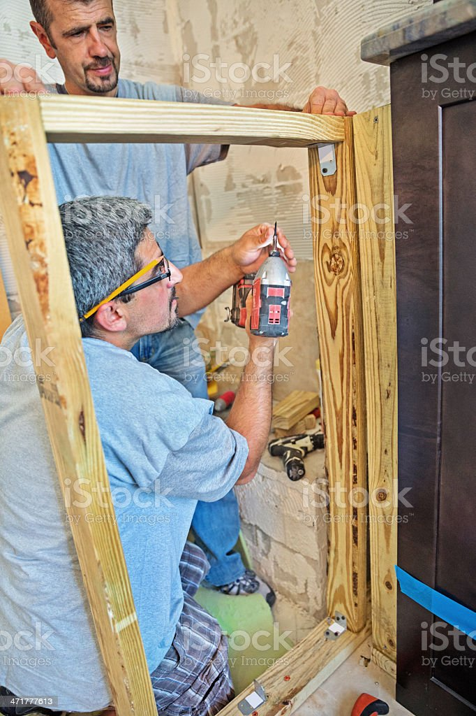 Workers construct a wooden frame for shower royalty-free stock photo