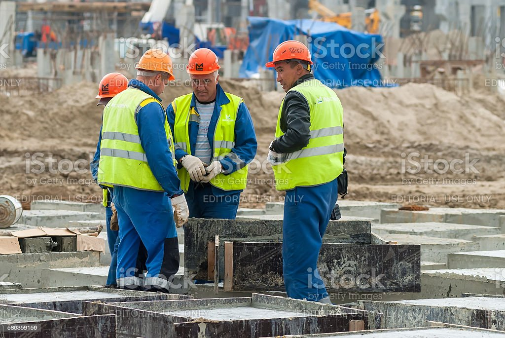 Workers do base under big oil tank stock photo