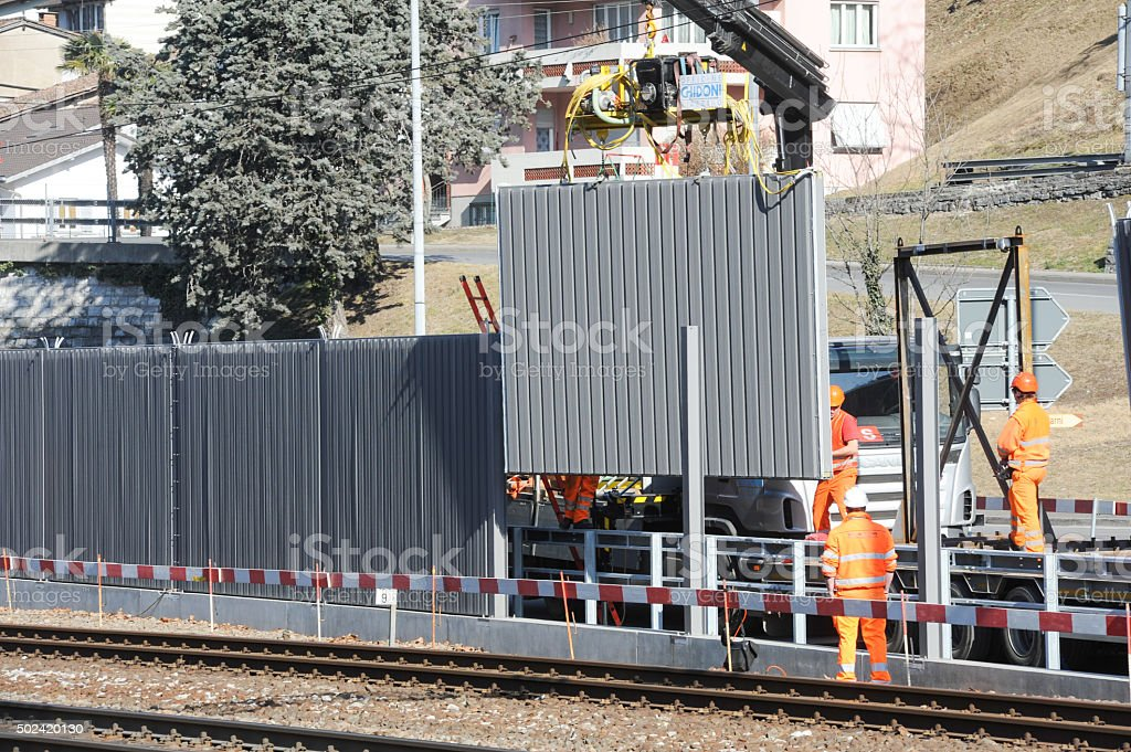Workers during the installation of noise barriers on the railway stock photo