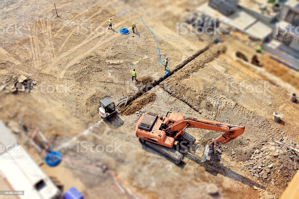 Workers, Engineers digging in ground, sewer system, street, tilt-shift, above stock photo