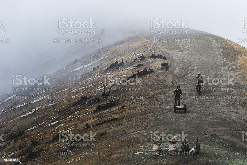 Workers extracting sulphur inside Kawah Ijen volcano crater stock photo