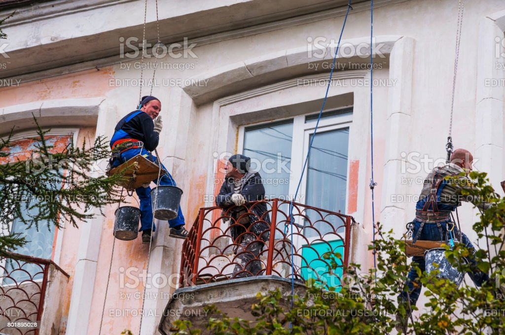 Workers for hire repair the facade of an apartment building on the city of Magadan stock photo