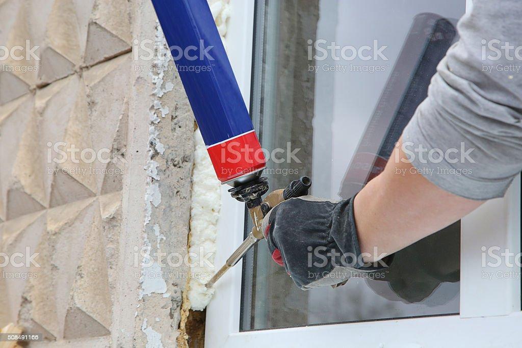 Worker's hand fix a window by  polyurethane foam stock photo