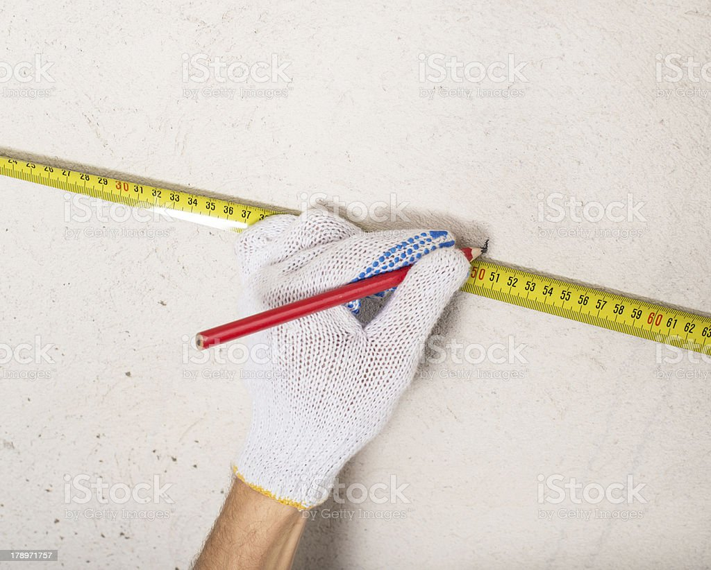 workers hand measuring plaster wall royalty-free stock photo