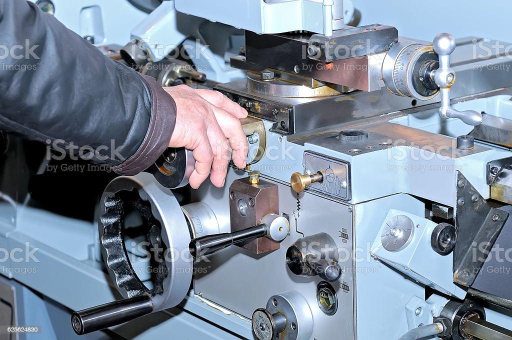 Worker's hand on the metalworking machine stock photo