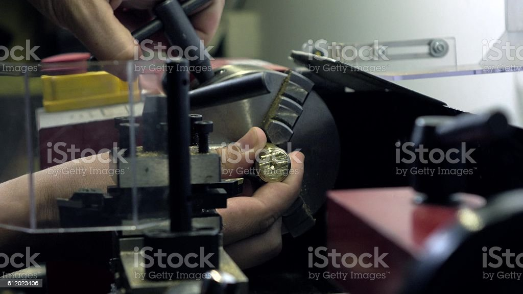 Worker's hands and lathe machine in action. Machining brass stock photo